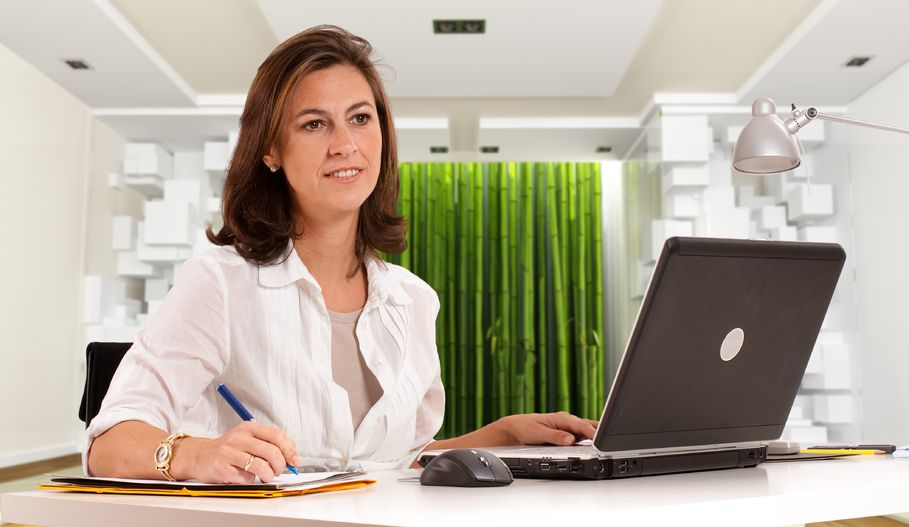 13354617 - woman sitting at her desk on an cool office environment
